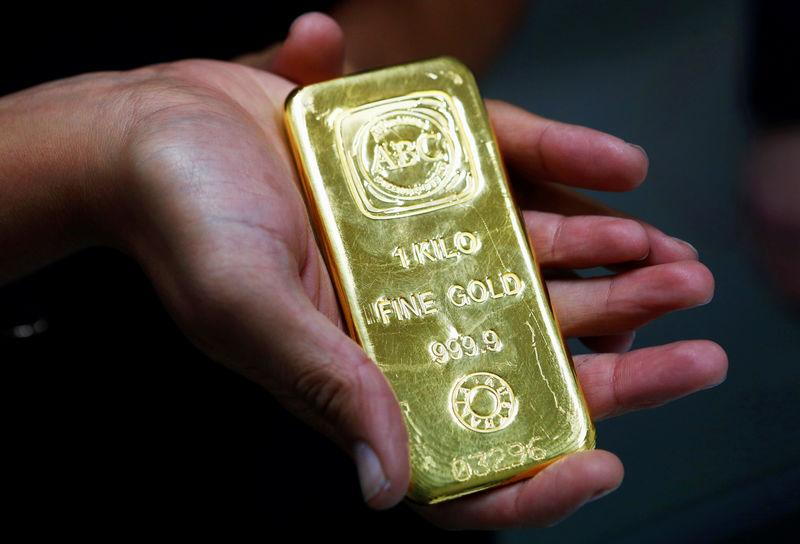 FILE PHOTO: A woman holds a 1 kg gold bar at the headquarters of the Australian Bullion Company in Sydney