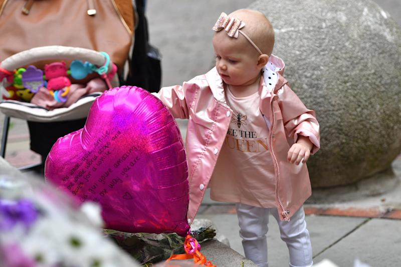 A young girl views flowers and balloons to the victims in Saint Anne's Square. (Getty Images)
