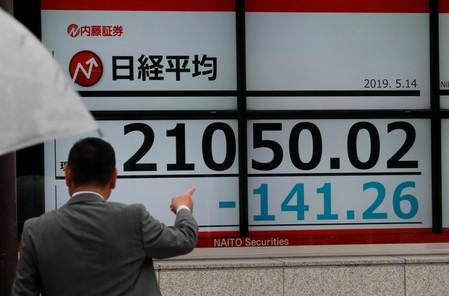 FILE PHOTO: A man points out an electronic board showing the Nikkei stock index outside a brokerage in Tokyo