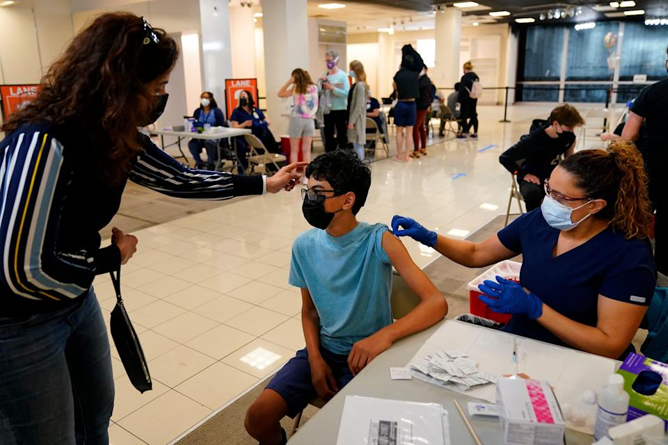 Nouf Albarakati, left, comforts her son Manaf Albarakati, 14, before he receives a COVID-19 vaccine from registered nurse Alicia Jimenez at a vaccination clinic in King of Prussia, Pa.