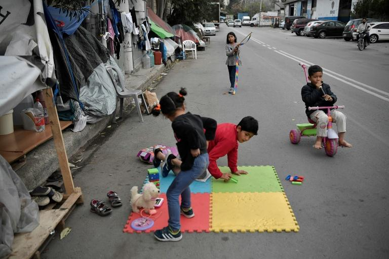 Children play near their families' tents set up on a street outside Eleonas refugee camp in Athens