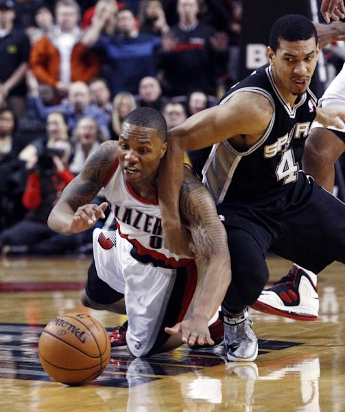 FILE- In this Dec. 13, 2012, file photo, Portland Trail Blazers guard Damian Lillard, left, battles for a loose ball with San Antonio Spurs forward Danny Green during the second half of an NBA basketball game in Portland, Ore. The Trail Blazers are expected to announce Lillard as the league's Rookie of the Year on Wednesday, May 1, 2013. (AP Photo/Don Ryan, File)