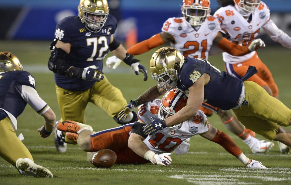 Clemson linebacker Baylon Spector, bottom center and Notre Dame running back Kyren Williams, right, scramble to grab a fumble during the Atlantic Coast Conference championship NCAA college football game, Saturday, Dec. 19, 2020, in Charlotte, N.C. Notre Dame recovered the ball. (Jeff Siner/The News & Observer via AP)