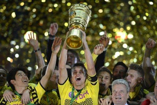 Dortmund's midfielder Sebastian Kehl (C) lifts the trophy next to teammates and German President Joachim Gauck (R)