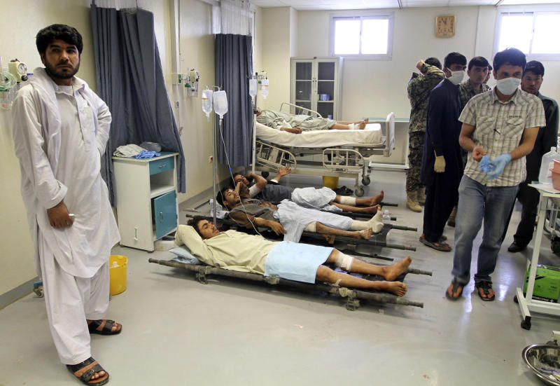 Afghan victims of a suicide attack are seen on stretchers at a hospital in Kandahar, south of Kabul, Afghanistan, Wednesday, June 6, 2012. Two suicide bombers blew themselves up in a market area in southern Afghanistan on Wednesday, killing and wounding scores of people, authorities said. (AP Photo/Allauddin Khan)