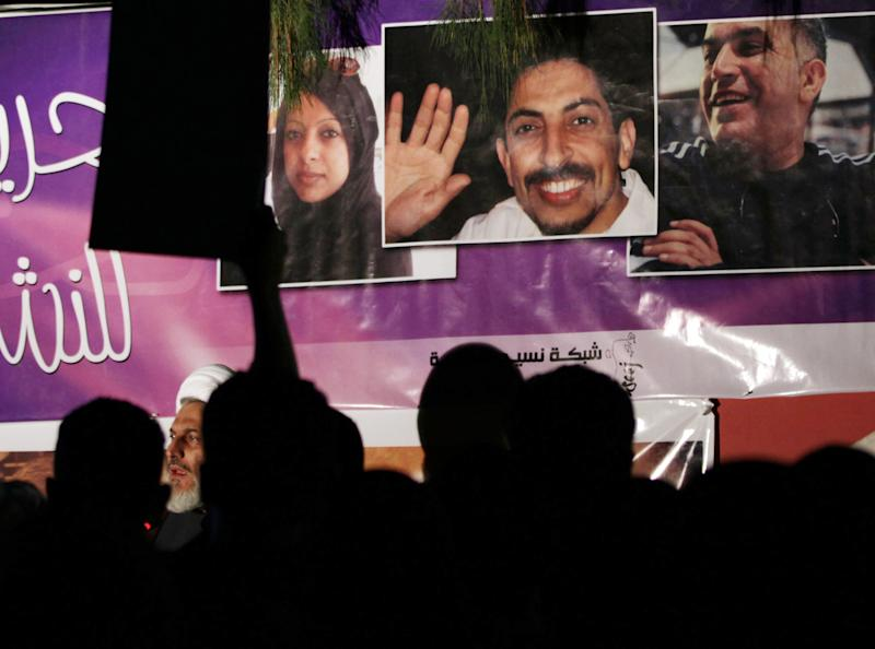 Bahraini anti-government protesters chant slogans in front of a banner calling for freedom for jailed rights activists Abdul Hadi al-Khawaja, center, Nabeel Rajab, right, and Zainab al-Khawaja left, during a rally outside the Rajab home in Bani Jamra, Bahrain, Monday, Dec. 10, 2012. A court session is scheduled for Tuesday in Rajab's appeal of a three-year sentence handed down for calling for and participating in unauthorized demonstrations. (AP Photo/Hasan Jamali)
