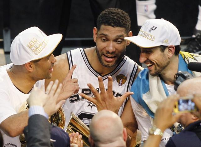 (L-R) San Antonio Spurs' Tony Parker of France, Tim Duncan, and Manu Ginobili of Argentina hold the Larry O'Brien trophy and gesture five fingers for Duncan's five championships after the Spurs defeated the Miami Heat in Game 5 of their NBA Finals basketball series in San Antonio, Texas, June 15, 2014. REUTERS/Mike Stone (UNITED STATES - Tags: SPORT BASKETBALL)