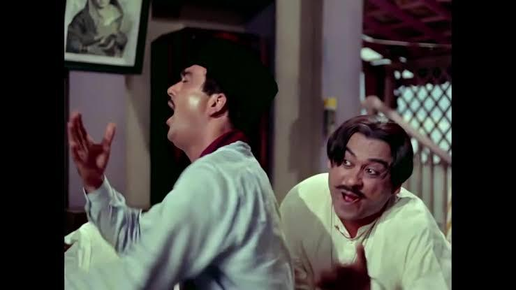 The pan-chewing sly music master helping his naive disciple to win the damsel next-door was quite the center of all the laughs <em>Padosan </em>evoked. Kishor Kumar in his crisp white <em>kurta </em>and Bengali <em>dhoti</em>, flaunting an oiled and mid-partitioned hair-do, remains etched in our memories for his fine rendition of singer and theatre actor, 'Vidyapati'. Just an after thought: Can say Kishore Kumar did the Radhe Bhaiya hairstyle before it was cool?