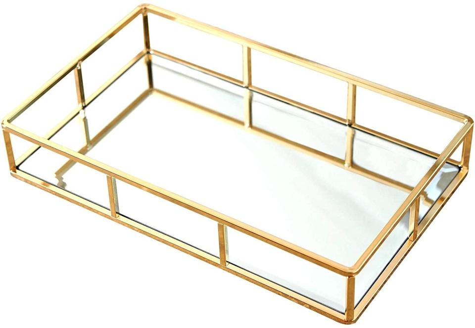 <p>Organize your perfumes, most-used makeup, jewelry, and more with this regal <span>PuTwo Gold Tray Mirror Vanity Tray</span> ($28).</p>