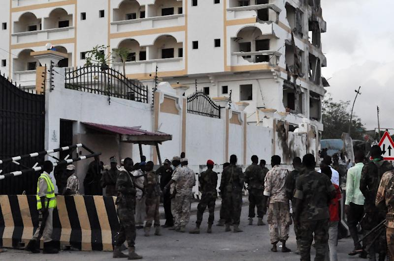 Somali soldiers stand in front of the damaged Jazeera Palace hotel following a suicide attack in Mogadishu on July 26, 2015 (AFP Photo/)