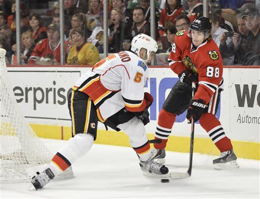 Chicago Blackhawks' Patrick Kane, right, passes the puck as Calgary Flames' Mark Giordano defends during the second period of an NHL hockey game, Friday, April 26, 2013 in Chicago. (AP Photo/Brian Kersey)