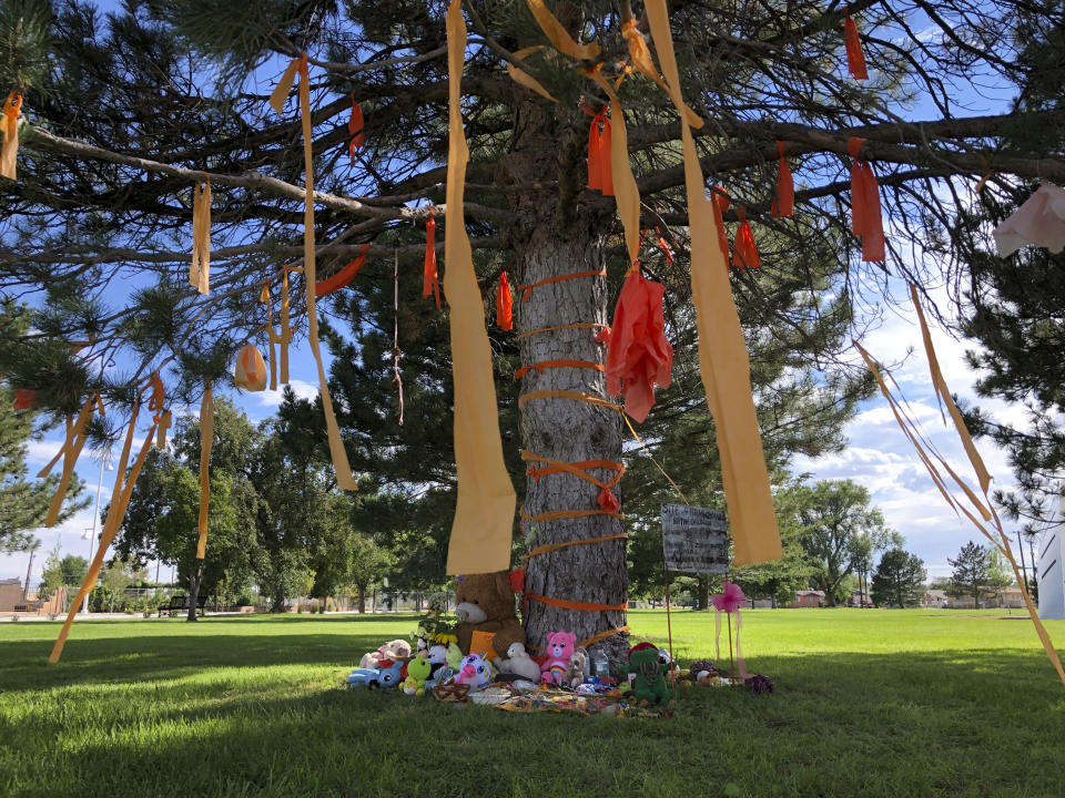 FILE - In this July 1, 2021, file photo, a makeshift memorial for the dozens of Indigenous children who died more than a century ago while attending a boarding school that was once located nearby is growing under a tree at a public park in Albuquerque, N.M. Albuquerque city officials plan to use ground-penetrating radar as they research the history of a site where dozens of Native American boarding school students are believed to have been buried more than a century ago. (AP Photo/Susan Montoya Bryan, File)