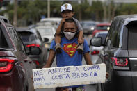 """FILE - In this April 26, 2021 file photo, Jeferson Alves, 35, carries his 3-year-old son Jonathan Miguel on his shoulders when asking for a handout, as he holds a sign written in Portuguese that reads """"Help me buy a basic food basket. Thank you,"""" on an avenue in Brasilia, Brazil. Alves says he worked at a construction company for two years and that at the end of last year he was fired because of the pandemic. Now he seeks donations and money on the streets to support his family. (AP Photo/Eraldo Peres, File)"""