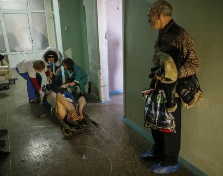 Medics help an injured Ukrainian serviceman as a local resident looks on at a hospital in Artemivsk February 8, 2015. REUTERS/Gleb Garanich