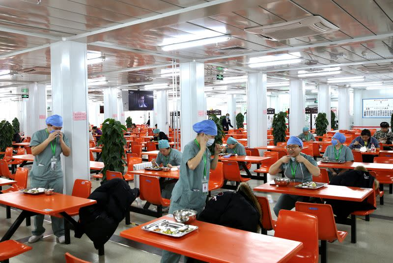 Medical workers eat at separate tables at a canteen inside Xiaotangshan Hospital in Beijing