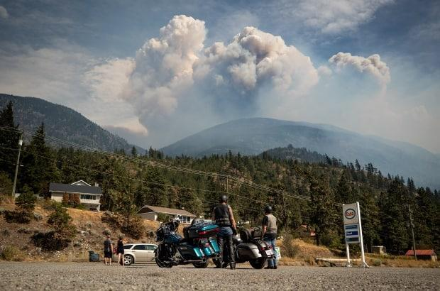 Motorcyclists stopped at a gas station watch as a pyrocumulus cloud, also known as a fire cloud, produced by the Lytton Creek wildfire rises into the sky from the fire burning in the mountains above Lytton, B.C., on Sunday.  (THE CANADIAN PRESS/Darryl Dyck - image credit)