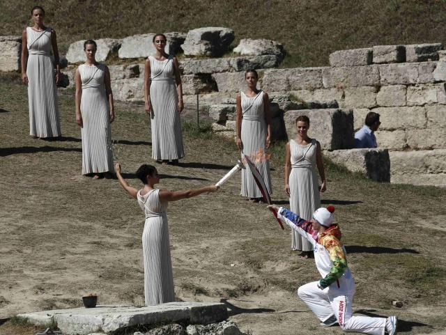 Greek actress Ino Menegaki playing the role of High Priestess passes the Olympic flame to Greek skier Yannis Andoniou (R), the first torchbearer of the 2014 Sochi torch relay, during a torch lighting ceremony of the Sochi 2014 Winter Olympic Games at the site of ancient Olympia in Greece September 29, 2013. The Sochi 2014 Winter Olympic torch was lit in ancient Olympia on Sunday, heralding the start of what will be the longest torch relay for any Winter Games, including a trip to space. REUTERS/Yorgos Karahalis (GREECE - Tags: SPORT OLYMPICS ENTERTAINMENT)