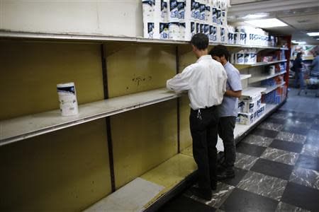 Supermarket staff work next to partially empty shelves of toilet paper in Caracas