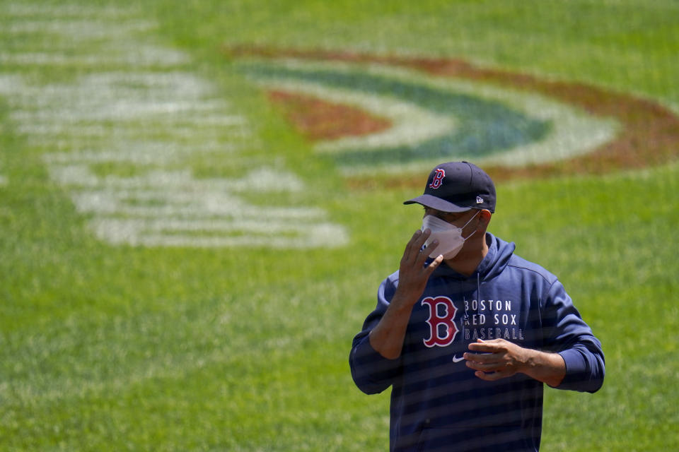 Boston Red Sox manager Alex Cora sends signs to third base coach third base coach Carlos Febles during the first inning of a baseball game against the Baltimore Orioles, Sunday, April 11, 2021, in Baltimore. (AP Photo/Julio Cortez)