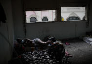 Actress Kelly Regina da Silva lies on a cushion watching TV in the building where she lives in one of the city center's squats, in Rio de Janeiro, Brazil, Tuesday, March 16, 2021. The Brazilian government's emergency pandemic aid program provided a lifeline to nearly 70 million poor and unemployed Brazilians which ended in December for da Silva. (AP Photo/Silvia Izquierdo)