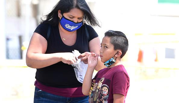 A child takes a COVID-19 test at a walk-in Coronavirus test site in Los Angeles, California.
