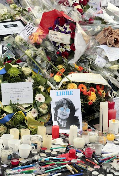 A picture of French late cartoonist Jean Cabut aka Cabu, flowers, candles and pens are placed at the entrance of the French weekly newspaper Charlie Hebdo's editorial office, on January 9, 2015 (AFP Photo/Jacques Demarthon)