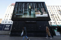 People walk past a giant screen streaming a Fendi fashion live show during the Milan's fashion week in Milan, Italy, Friday, Jan. 15, 2021. (AP Photo/Antonio Calanni)