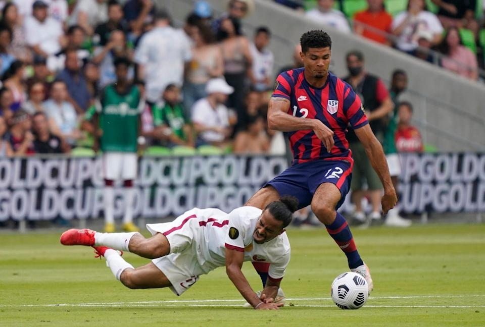 Jul 29, 2021; Austin, Texas, USA; Qatar forward Akram Afif (11) falls to the ground as United States defender Miles Robinson (12) dribbles past in the first half of a Concacaf Gold Cup semifinal soccer match at Q2 Stadium.