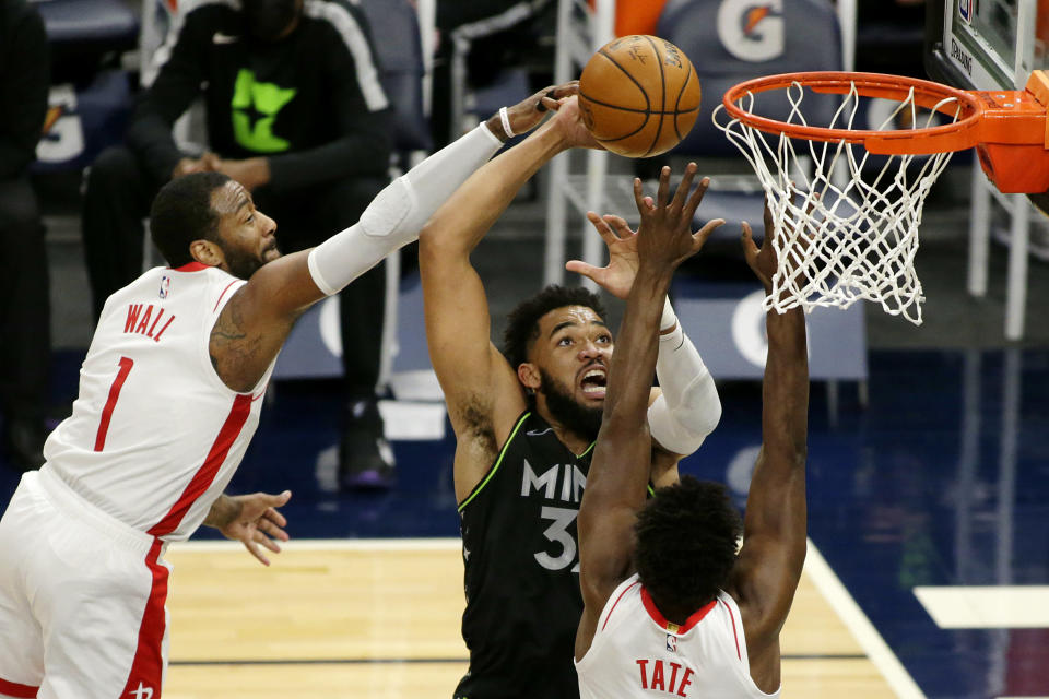 Minnesota Timberwolves center Karl-Anthony Towns (32) shoots against Houston Rockets guard John Wall (1) and forward Jae'Sean Tate (8) in the first quarter during an NBA basketball game, Friday, March 26, 2021, in Minneapolis. (AP Photo/Andy Clayton-King)