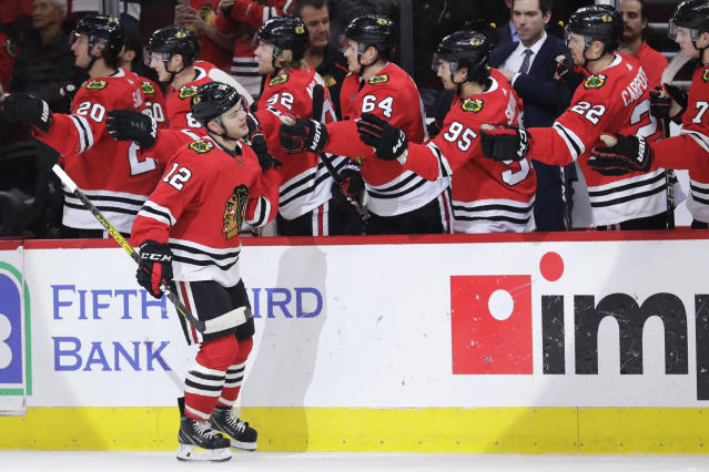 Chicago Blackhawks left wing Alex DeBrincat (12) celebrates with teammates after scoring a goal during the first period of an NHL hockey game against the Arizona Coyotes, Sunday, Dec. 8, 2019, in Chicago. (AP Photo/Nam Y. Huh)