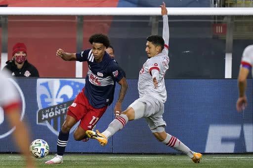 New England Revolution's Tajon Buchanan, left, vies for control of the ball with Toronto FC's Marco Delgado during the first half of an MLS soccer match Wednesday, Oct. 7, 2020, in Foxborough, Mass. (AP Photo/Steven Senne)