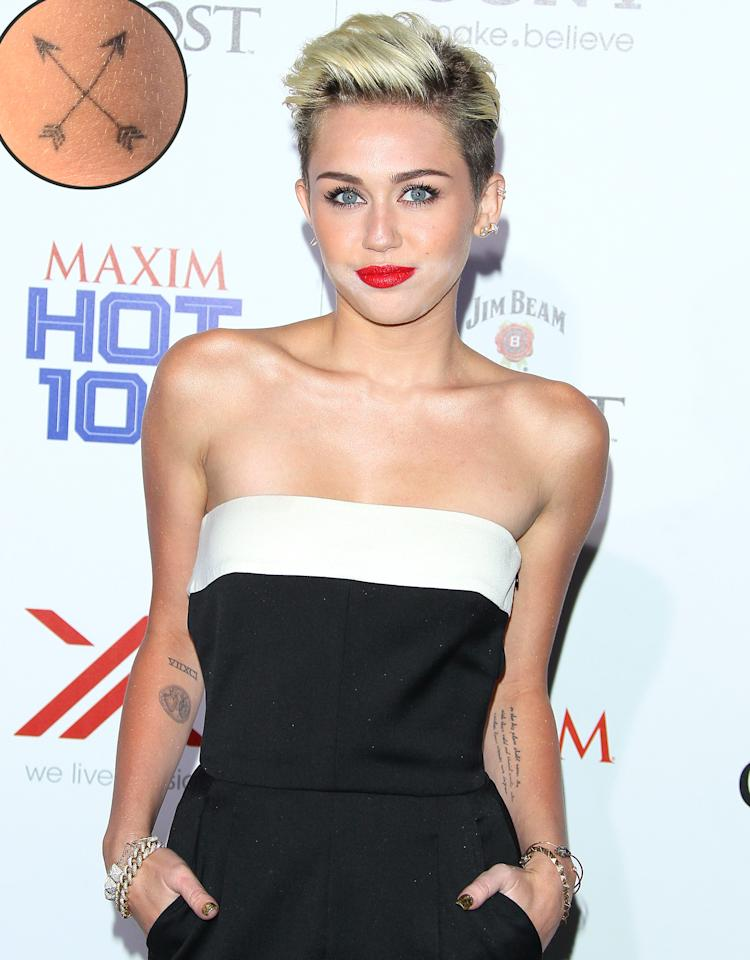 "Miley Cyrus's descent into tattoo addiction has been swift. She got her first tat when she was just 17. (She needed parental permission at that age, making Billy Ray and Tish enablers!) Now 20, the former Disney star has about 20 pieces of body art, including a skull tattoo on her ankle (which matches one fiancé Liam Hemsworth has) and an equal symbol on her ring finger to symbolize her support for gay marriage. In January, she turned to tattoo artist and reality star Kat Von D to etch a pair of crossed arrows, the Native American symbol for friendship, on the back of her right elbow. Later, Von D also gave the ""We Can't Stop"" singer a da Vinci heart on her left forearm and, just this past week, a mystery tat that Cyrus has yet to unveil. Something tells us this won't be her last …"