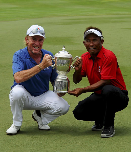 Miguel Angel Jimenez, left, of Spain and Thailand's Thongchai Jaidee, right, poses for the camera with the Eurasia trophy after both Team Asia and Euro drew during the third round of the Eurasia Cup golf tournament at the Glenmarie Golf and Country Club in Subang, Malaysia, Saturday, March 29, 2014.