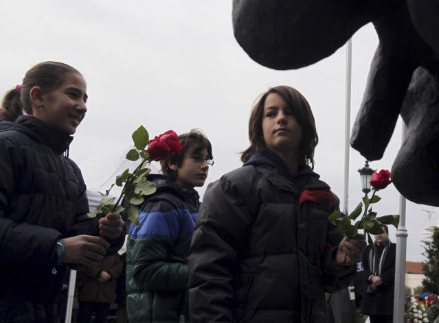 Children place flowers at the Holocaust Memorial commemorating the persecution of the Jewish people during World War II, in Thessaloniki, northern Greece, on Sunday, Jan. 27, 2013. There were some 50,000 Jews living in Thessaloniki at the start of World War II, and almost 45,000 perished at Auschwitz concentration camp, and Greece officially commemorates the Holocaust every Jan. 27. (AP Photo/Nikolas Giakoumidis)