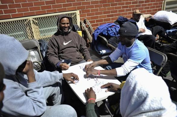 Job seekers play dominoes as they wait in front of the training offices of Local Union 46, the union representing metallic lathers and reinforcing ironworkers, in the Queens borough of New York, April 29, 2012.
