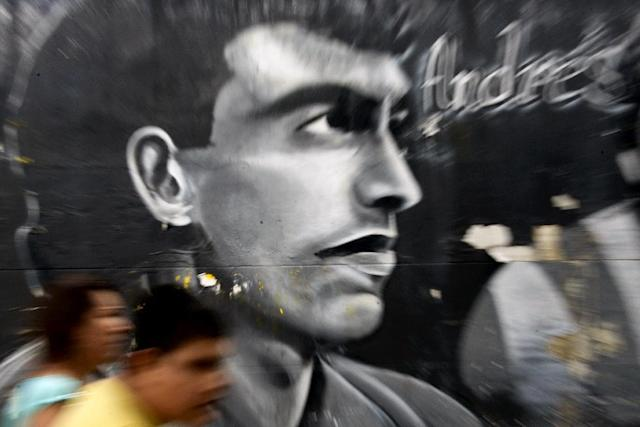 People walk by a mural painting depicting the late Colombian footballer Andres Escobar at the street in Medellin, Antioquia department, Colombia on July 1, 2014 (AFP Photo/Raul Arboleda)