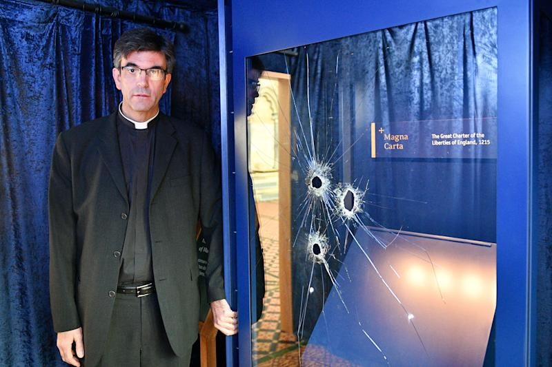 The Reverend Canon Nicholas Charles Papadopulos beside the glass case, which houses the Magna Carta, inside the Chapter House at Salisbury Cathedral with hammer holes in the glass after a 45-year-old man has been arrested on suspicion of its attempted theft.
