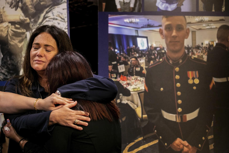 Christiana Sweetwood, mother of Marine Lance Corporal Chase Sweetwood, hand coming from left, Aleta Bath, mother of Private First Class Evan Bath and Lupita Garcia, mother of Marine Lance Corporal Marco Barranco embrace each other at a press conference next to a picture of Chase Sweetwood on Thursday, July 29, 2021, in Oceanside, Calif. The families of eight Marines and one sailor who died when their amphibious assault vehicle sank off the Southern California coast in the summer of 2020 plan to sue the manufacturer of the vehicle that resembles an armored seafaring tank, their lawyers announced Thursday. (Sam Hodgson/The San Diego Union-Tribune via AP)