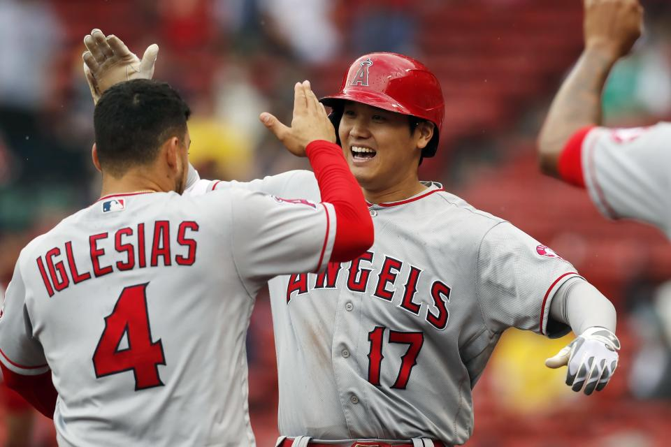 Los Angeles Angels' Shohei Ohtani (17) celebrates his two-run home run with teammate Jose Iglesias (4) during the ninth inning of a baseball game against the Boston Red Sox, Sunday, May 16, 2021, in Boston. (AP Photo/Michael Dwyer)