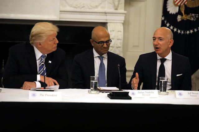 President Donald Trump and Satya Nadella, CEO of Microsoft Corporation listen as Jeff Bezos, CEO of Amazon, speaks during an American Technology Council roundtable at the White House in Washington, D.C., June 19, 2017.