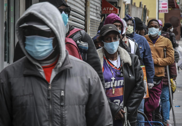 """People wait for a distribution of masks and food from the Rev. Al Sharpton in the Harlem neighborhood of New York, after a new state mandate was issued requiring residents to wear face coverings in public due to COVID-19, Saturday, April 18, 2020. """"Inner-city residents must follow this mandate to ensure public health and safety,"""" said Sharpton. The latest Associated Press analysis of available data shows that nearly one-third of those who have died from the coronavirus are African American, even though blacks are only about 14% of the population. (AP Photo/Bebeto Matthews)"""