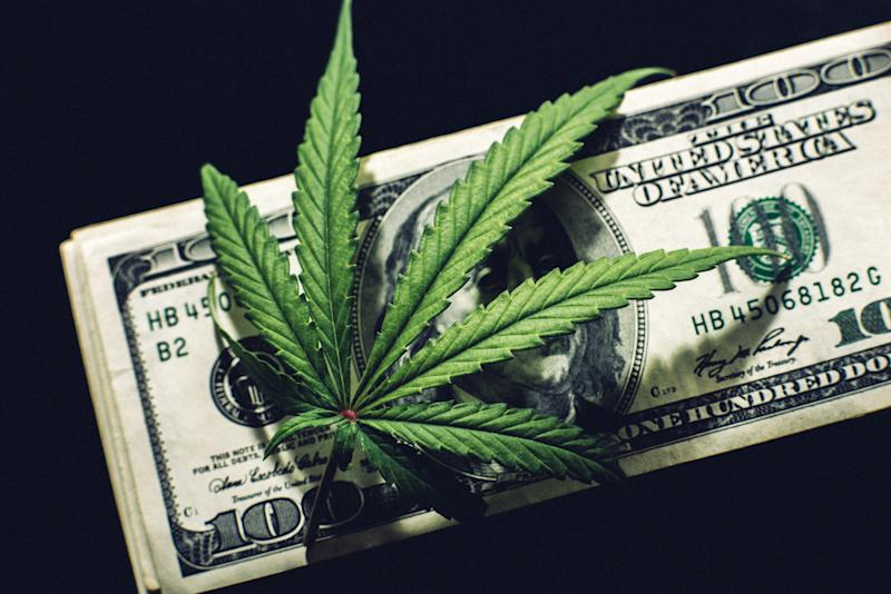 A cannabis leaf atop a neat stack of hundred dollar bills.