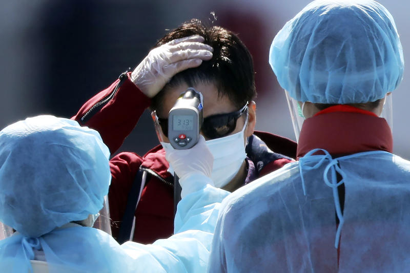 An official in protective suits measure the temperature of the foreign passengers disembarked from the quarantined Diamond Princess cruise ship before boarding to buses at a port in Yokohama, near Tokyo, Friday, Feb. 21, 2020. Japanese Prime Minister Shinzo Abe should be basking in the limelight this year in the runup to the 2020 Tokyo Olympics. Instead, the economy is reeling and criticism is mounting over his government's handling of a new virus that began in China and has spread alarmingly in Japan. (AP Photo/Eugene Hoshiko)