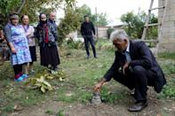 Locals gather near the remains of a shell in the Azerbaijani town of Beylagan on Sunday during the fighting between Armenia and Azerbaijan over the breakaway Nagorno-Karabakh region.
