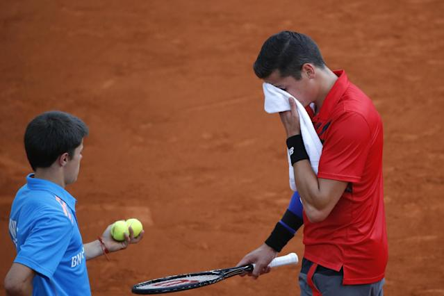 Canada's Milos Raonic wipes his face prior to serving during the quarterfinal match of the French Open tennis tournament against Serbia's Novak Djokovic at the Roland Garros stadium, in Paris, France, Tuesday, June 3, 2014. Djokovic won in three sets 7-5, 7-6, 6-4. (AP Photo/Michel Euler)
