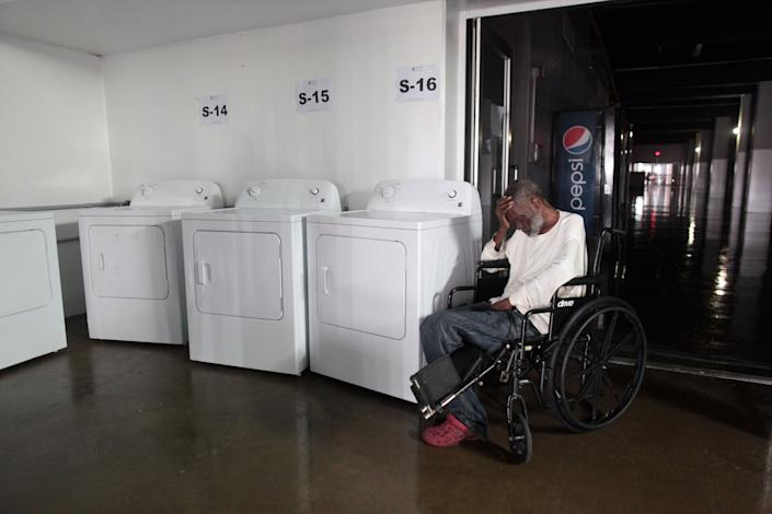 A man sits in a wheelchair next to washing machines at a shelter after the area was hit by Hurricane Maria, in San Juan, Puerto Rico September 22, 2017. Picture taken September 22, 2017. REUTERS/Alvin Baez