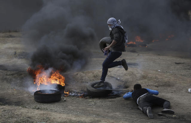 <p>Palestinian protesters burn tires during a protest on the Gaza Strip's border with Israel, May 14, 2018. (Photo: Khalil Hamra/AP) </p>