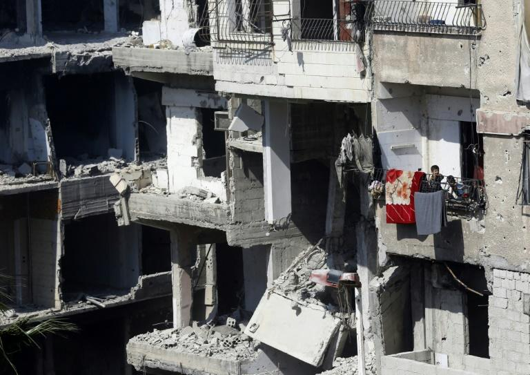Syrian children stand on a balcony of a destroyed building in Harasta, on the outskirts of the Syrian capital Damascus on July 15, 2018