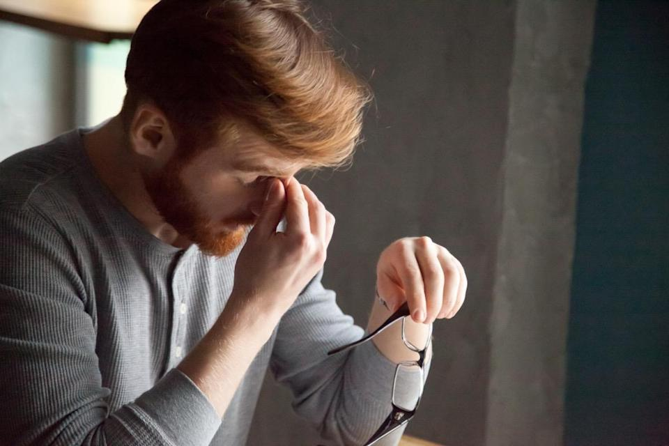 Tired red haired man take glasses off working too long at computer, exhausted millennial male suffer from headache or eye tension, young student massaging nose bridge feeling fatigue