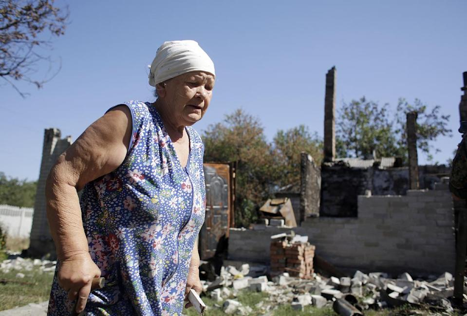 An woman walks beside her ruined house in Pervomayskiy, some 5 km northwest of Donetsk, eastern Ukraine, on September 6, 2014, a day after Kiev and pro-Russian rebels signed a ceasefire after five months conflict (AFP Photo/Anatolii Stepanov)